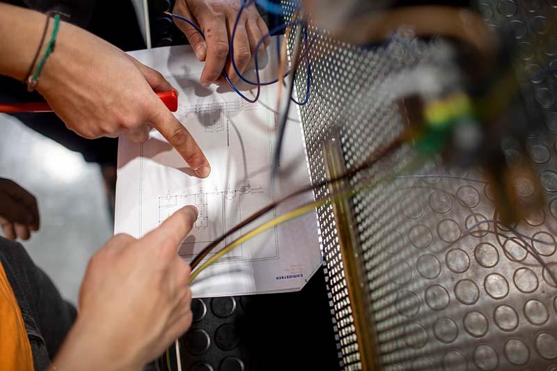 Alumnes analitzant un plànol d'un circuit elèctric dins del mòdul de Mecatrònica Industrial